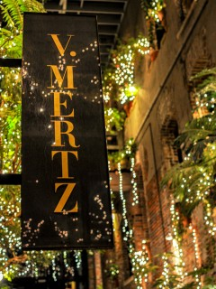 sparkly lights and greenery by V Mertz sign outside restaurant