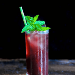 Blackberry cocktail in tall glass with mint and straw