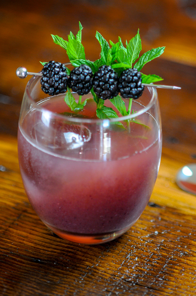 Honey Blackberry Whiskey Shrub Cocktail with clear ice. Blackberries and mint garnish.