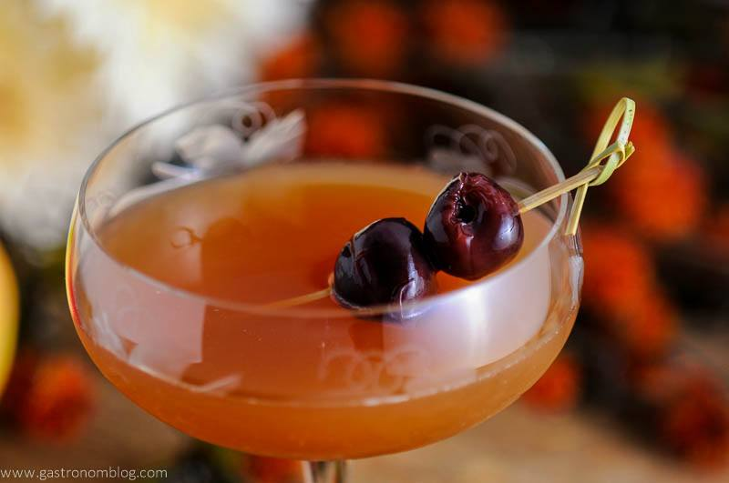 An Apple Cider Manhattan Cocktail in an etched coupe with brandied cherries on a cocktail pick with orange flowers in the background