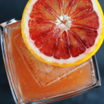 orange cocktail in rocks glass with orange slice on top