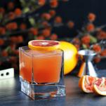 orange cocktail in rocks glass with orange slices