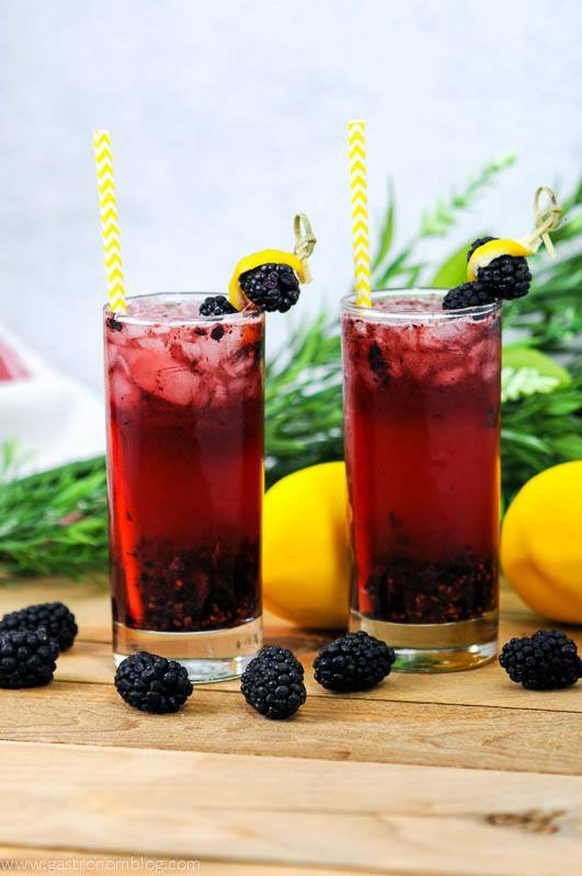 Muddled Blackberry Gin cocktai in two highball glasses with yellow straws. Garnished with blackberries and lemon peel. Flowers in the background.