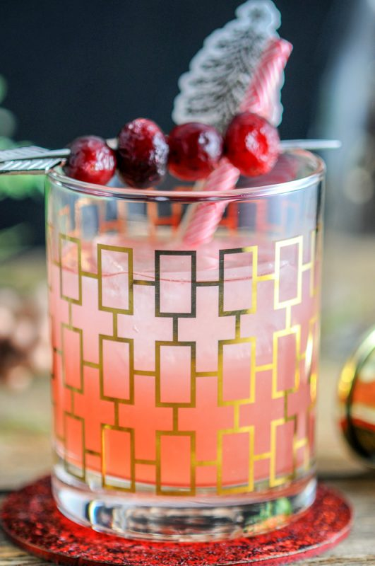 Red Hound Cranberry Vodka Cocktail in gold etched glass, gold jigger