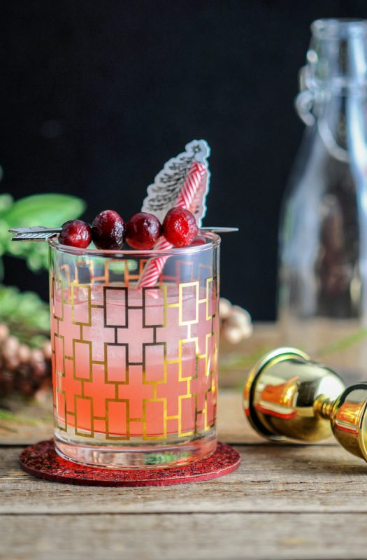 Red Hound Cranberry Vodka Cocktail in gold etched glass, gold jigger in background
