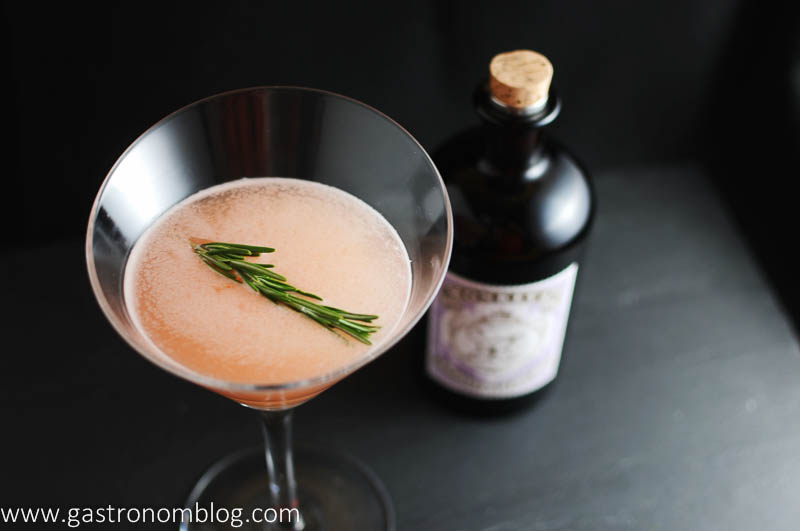 Top shot of gin and grapefruit cocktail with gin bottle