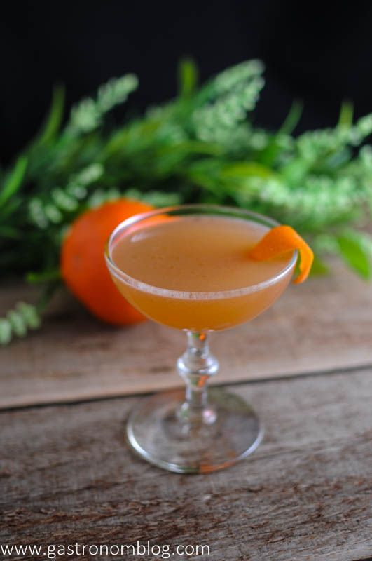 The Scofflaw Cocktail in a coupe on a wood board. Orange and leaves in background.