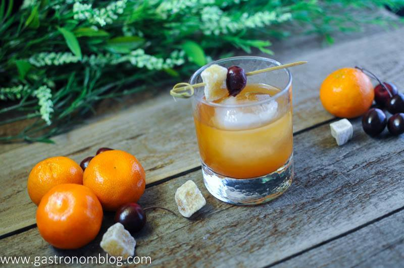 Ginger Clementine Old Fashioned Cocktail in a rocks glass with candied ginger, cherries and clementines on a wooden board