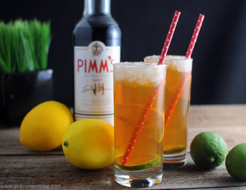 Pimm's Cup Cocktail in highballs with lemons and limes. Pimm's bottle and plant in background