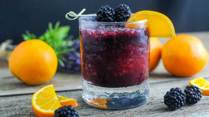 rambler Cocktail in a rocks glass with oranges and blackberries