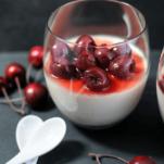 White panna cotta in glass with cherries, white spoons, cherries