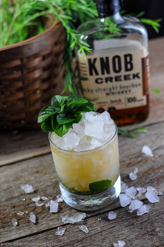 Mint Julep in a rocks glass with mint and heaped ice. Knob Creek bourbon bottle and basket in background
