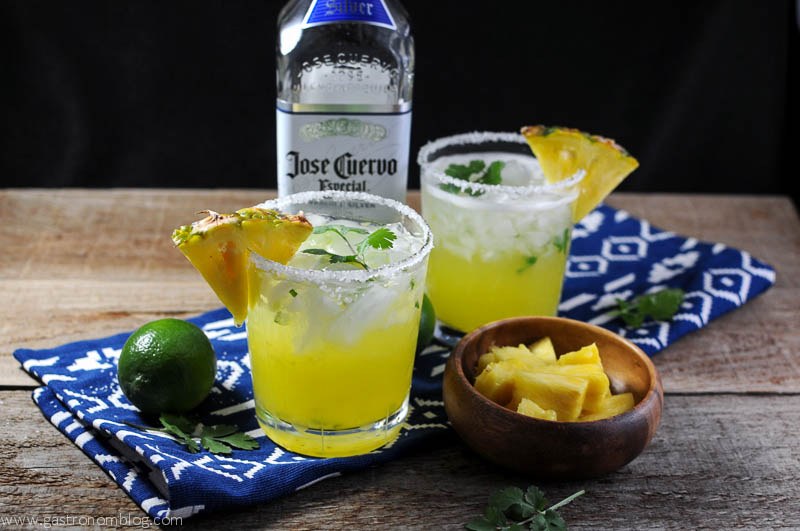 Pineapple Cilantro Margarita with blue and white napkin, bowl of pineapple and limes with a tequila bottle on a wood background