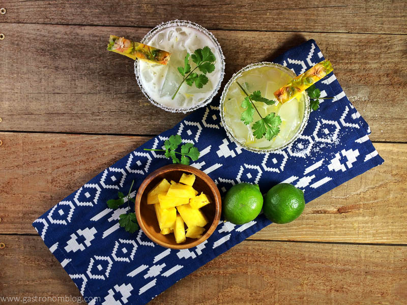 Pineapple Cilantro Margarita top shot with blue and white napkin, bowl of pineapple and limes on a wood background