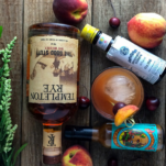 Top shot of peach cocktail and ingredients with whiskey bottle, bitters, peachs and hot sauce