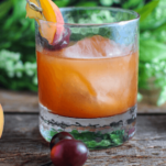 Peach Old Fashioned cocktail in rocks glass, peaches and cherries