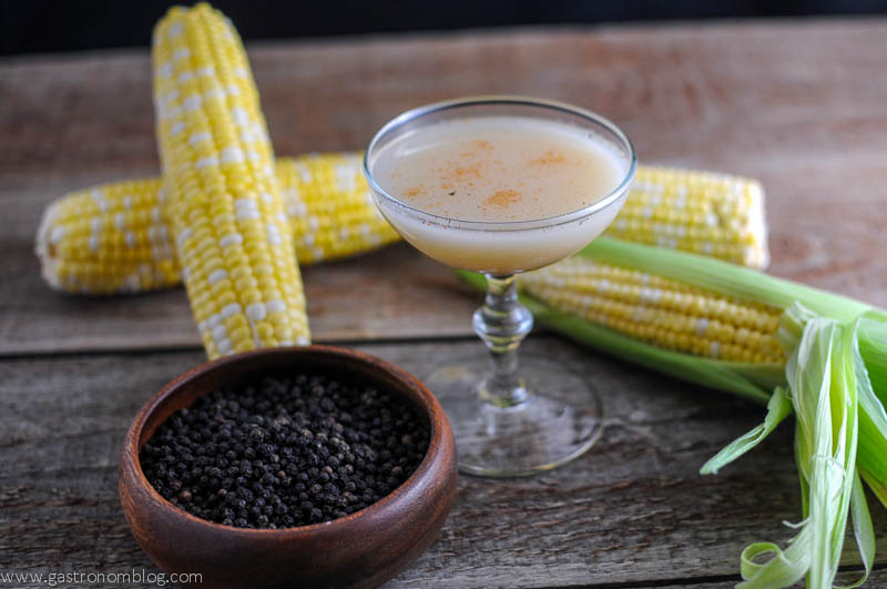 The Nebraskan Cocktail in a coupe with ears of corn, jigger and wooden spoon. Bottles of ginger beer and vodka in background