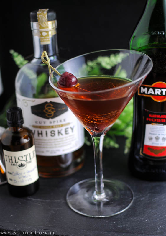 Chocolate Manhattan Cocktail in a Martini glass, cherry on a cocktail pick. Bottles of bitters, whiskey and sweet vermouth in the background