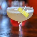 Yellow cocktail with egg white topper in a coupe, lemon peel pinned to side of glass