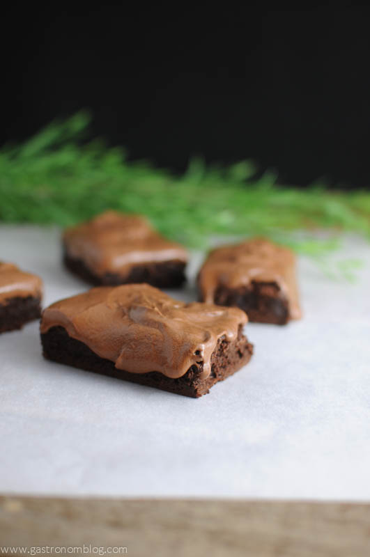 Root Beer Whiskey Brownies on parchment with greenery in background