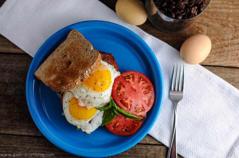 Bacon, Egg, Tomato Breakfast Sandwich on a blue plate with eggs and coffee in the background