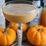 Pumpkin cocktail in a coupe with pumpkins and bottles behind