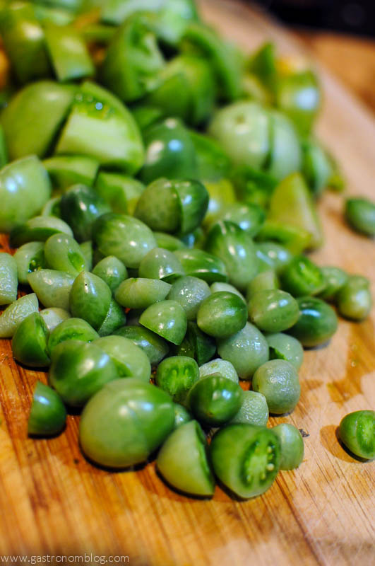 Green Tomato Jam - pile of green tomatoes on cutting board.