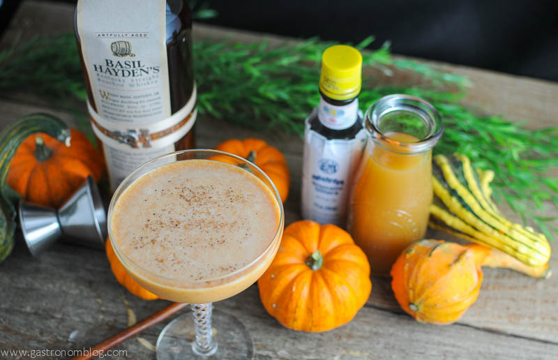 Pumpkin Harvest Cocktail in a coupe. Pumpkins behind with bottles