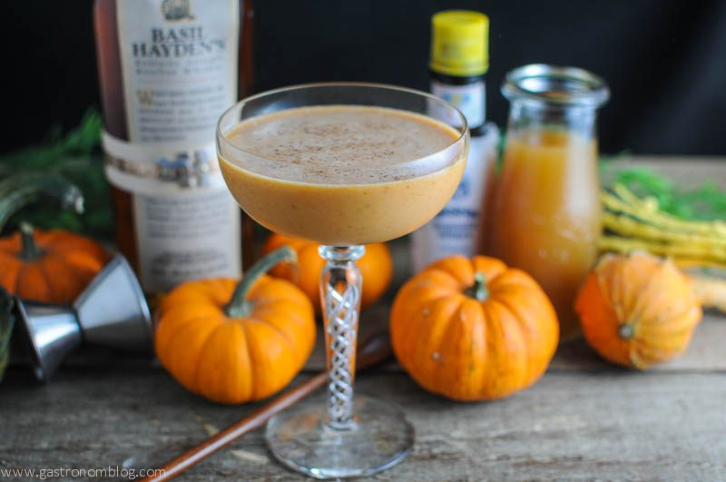 Pumpkin Harvest cocktail in cocktail coupe with mini pumpkins and jiggers, whiskey bottle and bitters bottle in background