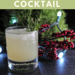 Rosemary's Pear Cocktail - opague cocktail with ice in rocks glass, greenery and lights behind