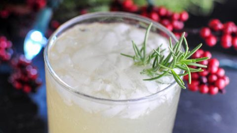 Rosemary's Pear cocktail in a rocks glass, lights and greenery behind