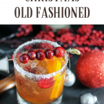 Christmas Old Fashioned - gold cocktail in rocks glass with sugar rim and cranberries on a pick. Christmas ornaments and red flowers behind