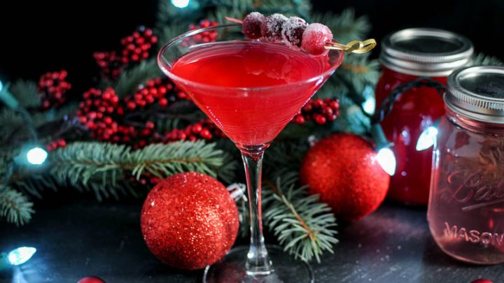 Red cocktail in martini glass with cranberries on pick. Evergreen and Christmas ornaments in background with red syrup filled jars