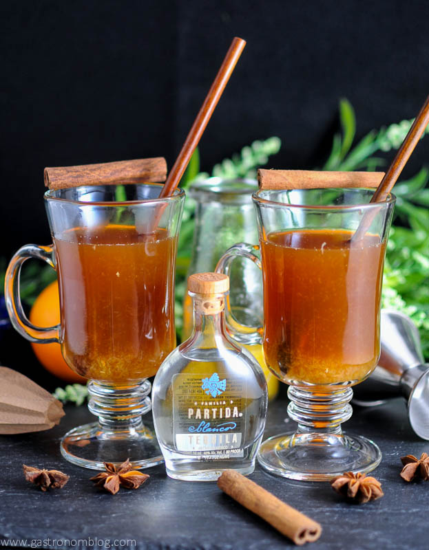 Tequila Hot Toddy in mugs with cinnamon sticks and wooden spoons