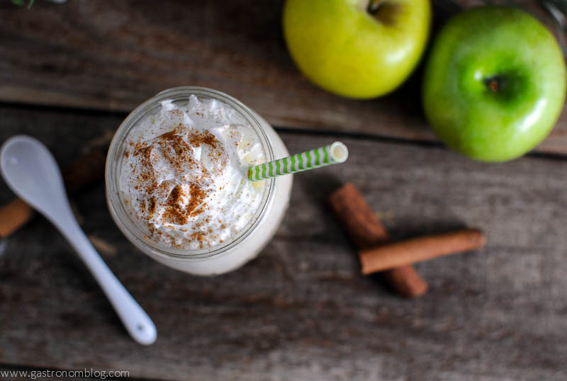 Drunken Apple Pie Milkshake with amaro bottle in background. Apples, cinnamon sticks, ceramic spoons