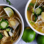 Pho soup in white bowls with limes and sprouts on top