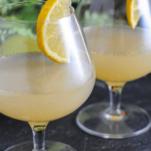 Yellow cocktail in balloon glass, lemon slice