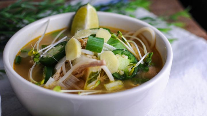 Chicken Pho in a white bowl on a white napkin. Topped with jalapeno and lime slices