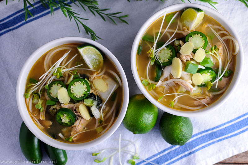 Crockpot Pho in two bowls, jalapenos, limes and sprouts on a white napkin. Slowcooker pho