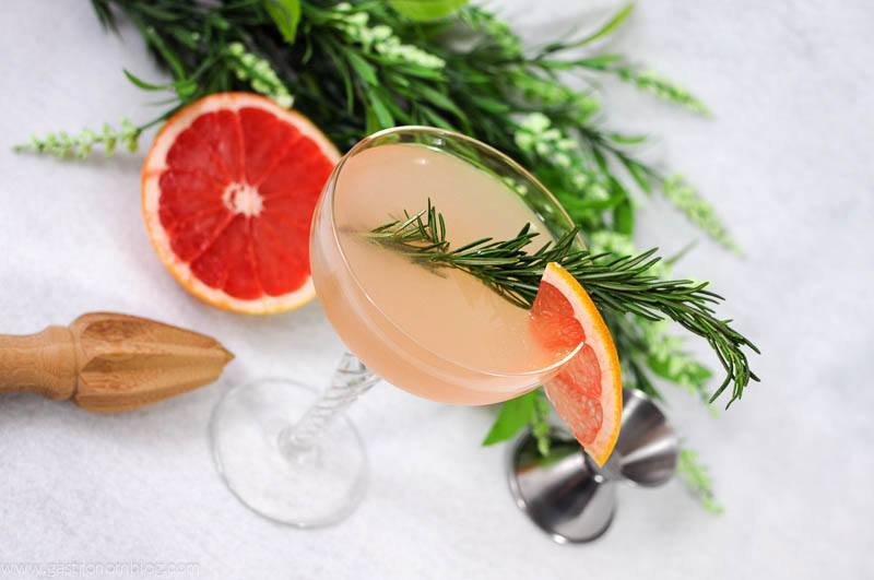 French Tart cocktail in coupe with grapefruit wheel and rosemary sprig. Grapefruit with flowers in the background