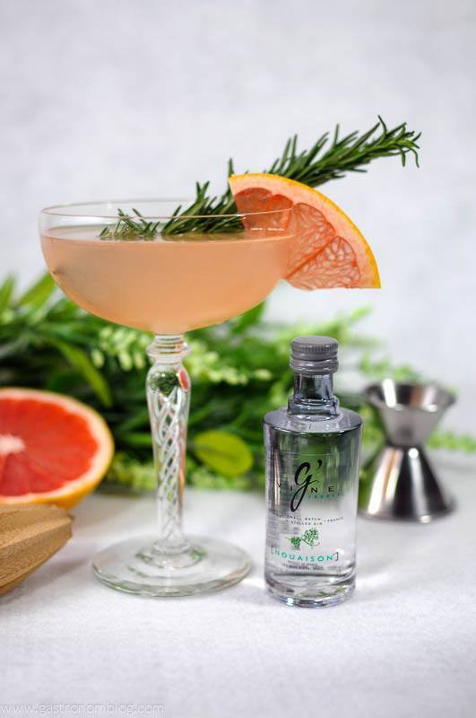 French Tart cocktail in coupe with grapefruit wheel and rosemary sprig. Grapefruit and gin bottle with flowers in the background