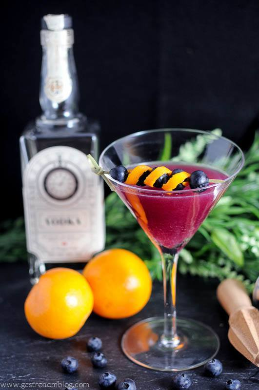 Garnet Martini in a martini glass, gin bottle behind, oranges and greenery