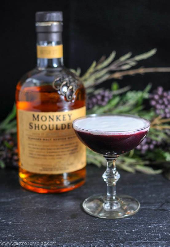 The Black Scot cocktail in a cocktail coupe, Monkey Shoulder whisky bottle and flowers in background for this scotch cocktail