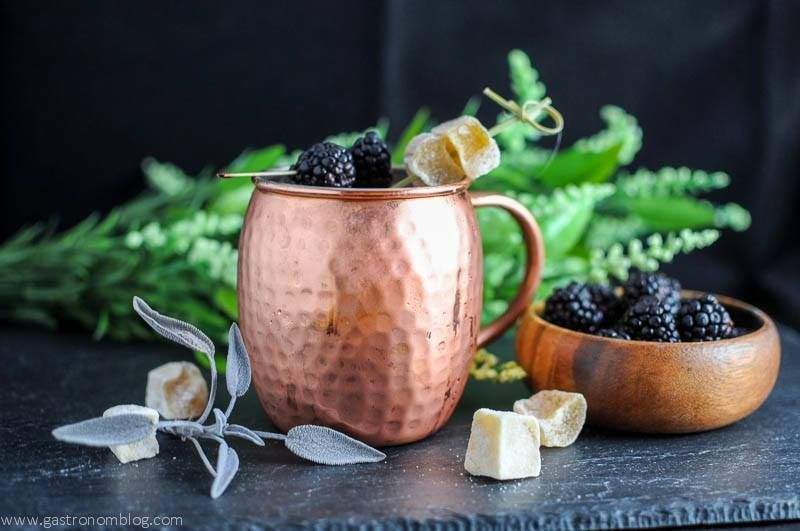 Blackberry Sage Kentucky Mule in a copper mug, wooden bowl of blackberries, greenery in background