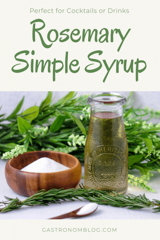 Rosemary Simple Syrup in a bottle, wood bowl of sugar and spoon. Flowers behind.