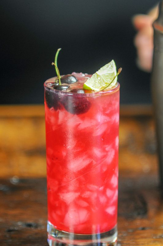 Cherry Cocktail in a highball with a lime and cherries