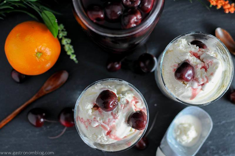 No Churn Old Fashioned Ice Cream in rock glasses with brandied cherries on top and in a jar. Orange, wooden spoons and cherries on slate board