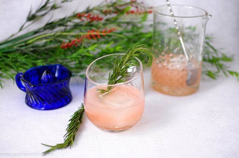 Pink cocktails in glasses with large ice cube. rosemary sprig garnish. Mixing glass in background with bar spoon, blue juicer, greenery behind