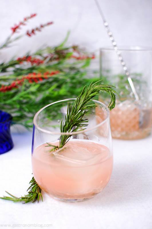 Rosada Cocktail with rosemary sprig and ice cube. Mixing glass and bar spoon with flowers in background
