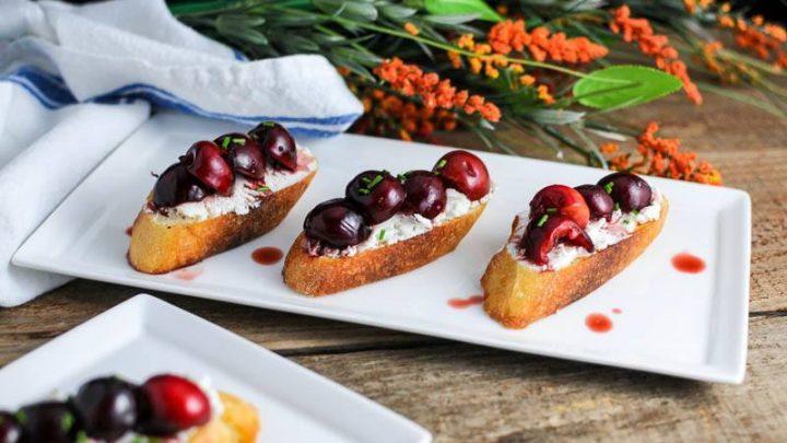 Cherry crostini on goast cheese toasts on white plates. Orange flowers and white napkin in background